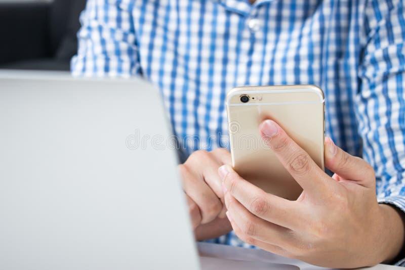 Fim acima O homem que veste camisas azuis está usando telefones para a compra em linha fotografia de stock royalty free