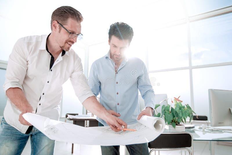 Fim acima os arquitetos discutem esboços do projeto novo foto de stock