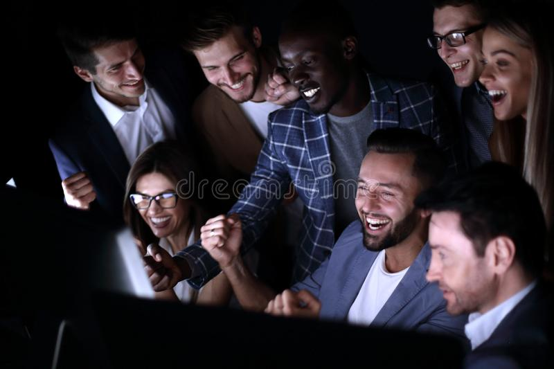 Fim acima Os executivos alegres olham o tela de computador foto de stock