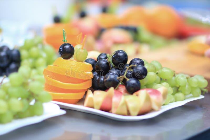 Fim acima placas com uvas e frutos no fundo borrado foto de stock