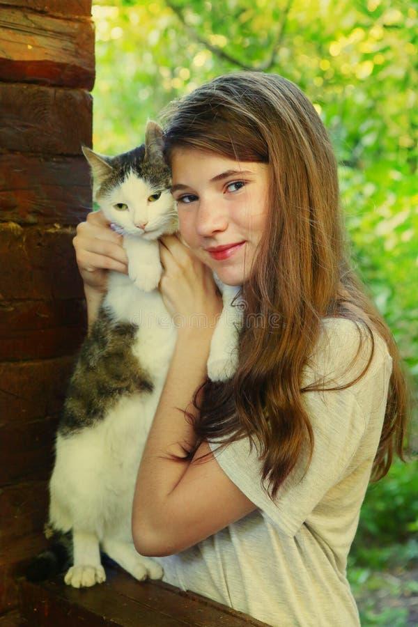 Fim adolescente do gato do abraço do gril acima da foto fotografia de stock royalty free