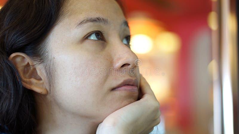 Fim asiático da menina da raça misturada acima da cara Olhar acima pensa e espera fotos de stock royalty free