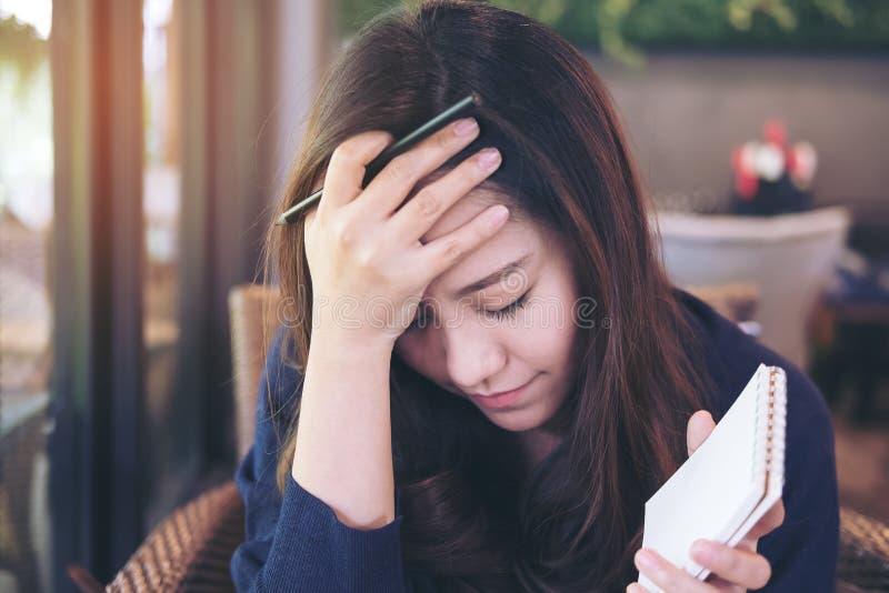 Fim asiático da mulher de negócio seus olhos que guardam o caderno e o lápis com o sentimento forçado e cansado imagem de stock royalty free