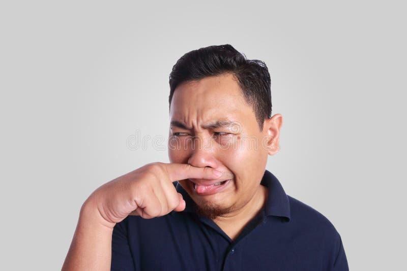 Fim asiático do homem o seu doente do nariz do cheiro mau fotos de stock