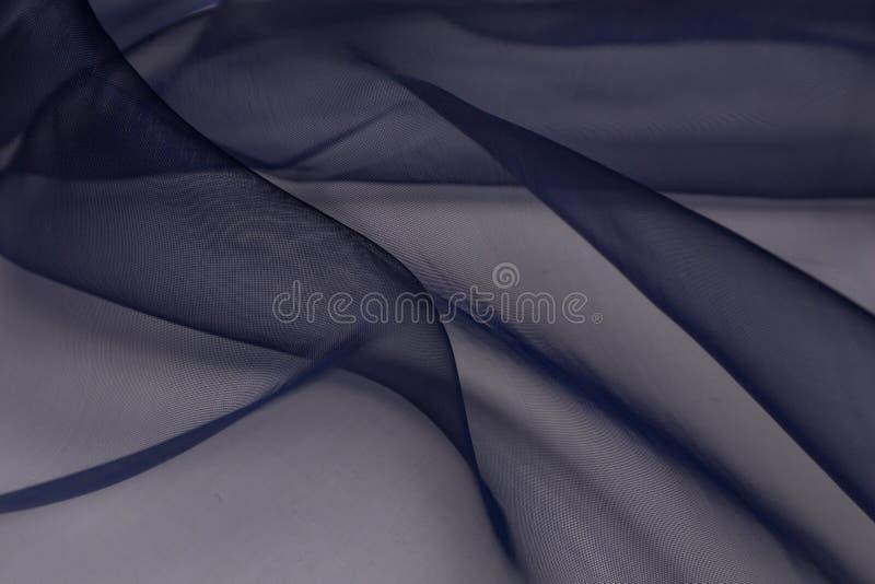Fim bonito acima da tela de seda azul com fundo da textura de matéria têxtil fotografia de stock royalty free