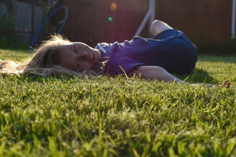 Fim bonito da moça acima na grama verde no verão Cara nova de sorriso da menina fotografia de stock