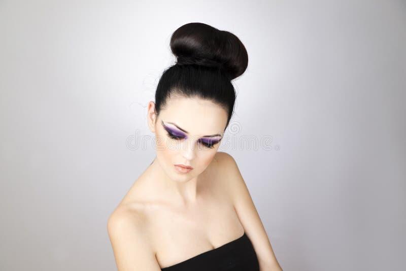 Fim bonito profissional da jovem mulher da composição e do penteado acima imagem de stock royalty free