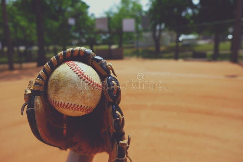 Fim da bola e da luva da estação de basebol acima com campo no fundo fotografia de stock royalty free