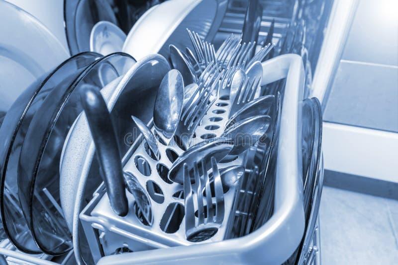 Fim da máquina da máquina de lavar louça acima, pratos, raposas das colheres da cutelaria e facas em uma bandeja plástica imagem de stock royalty free