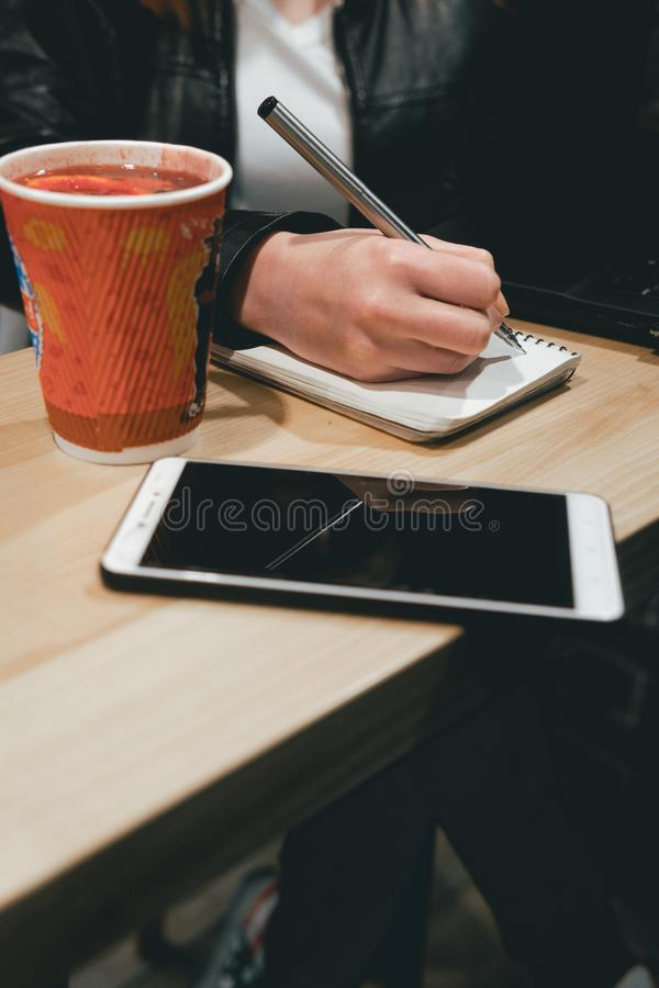 Fim da mão da menina acima de guardar uma pena, escrevendo em um caderno, portátil no café, smartphone, pena, computador do uso O imagens de stock