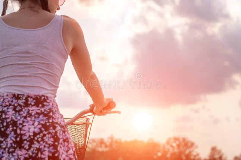 Fim da menina acima com a bicicleta no por do sol do ver?o na estrada no parque da cidade Completando o ciclo a rua para trabalha imagens de stock royalty free