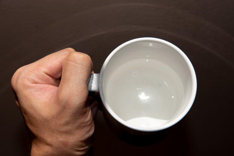 Fim da vista superior acima da bebida da água da posse da mão no copo branco fotografia de stock royalty free