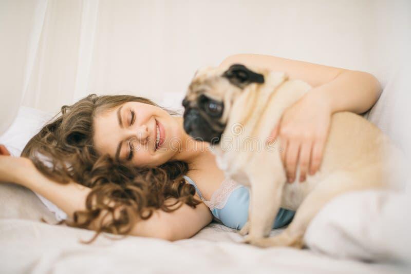 Fim de semana bonito da família Mulher que relaxa na cama com cão do pug foto de stock