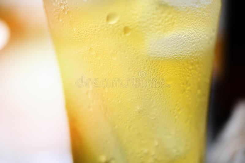 Fim de vidro das bolhas da cerveja acima da cerveja da caneca com gota da água no fundo do bar imagem de stock