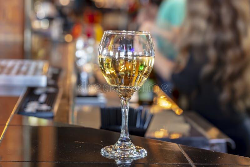 Fim do baixo ângulo acima do vidro de vinho da perspectiva na barra superior contrária de madeira imagem de stock