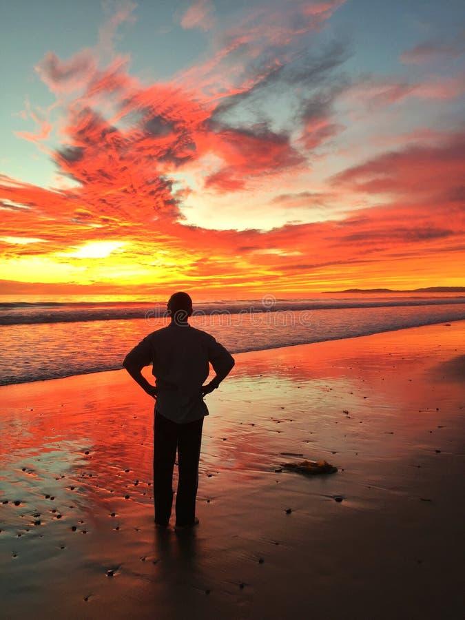 Fim do dia onde um homem para para apreciar um por do sol bonito de Califórnia imagens de stock