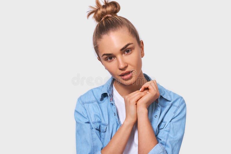 Fim do estúdio acima do retrato da jovem mulher loura europeia adorável com o penteado do bolo vestido na posição azul da camisa  foto de stock royalty free