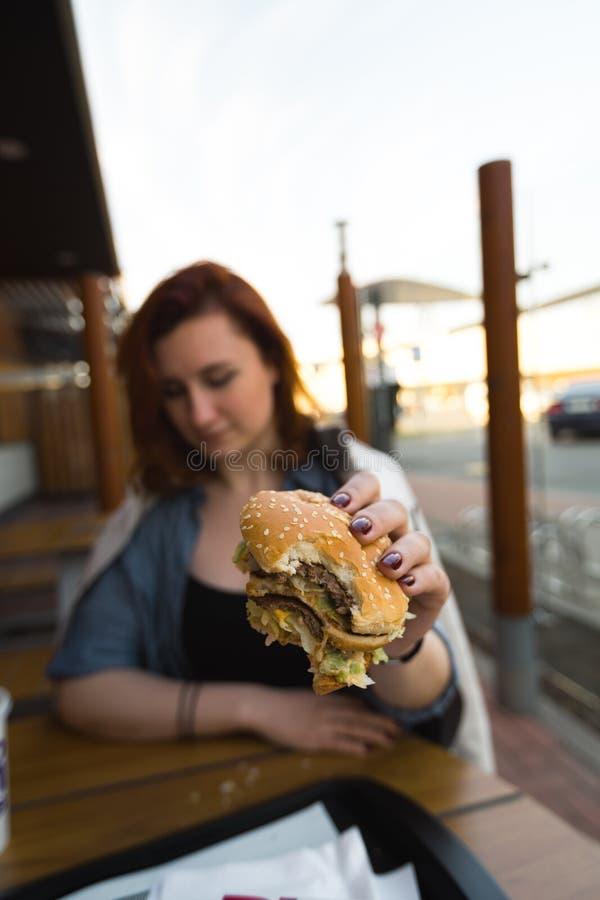 Fim do Hamburger acima - jovem mulher que come no restaurante do fast food - do cheeseburger, das fritadas m?dias e da soda fotos de stock