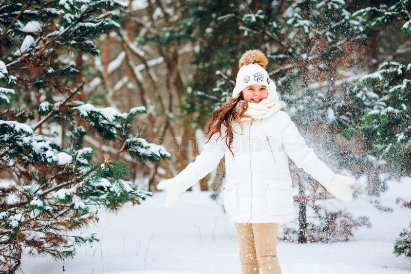 Fim do inverno acima do retrato da menina sonhadora bonito da criança no revestimento, no chapéu e nos mitenes brancos imagens de stock