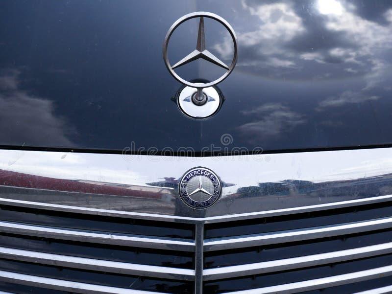 Fim do logotipo de Mercedes Benz acima do tiro, céu nebuloso refletindo na capa do motor imagens de stock royalty free