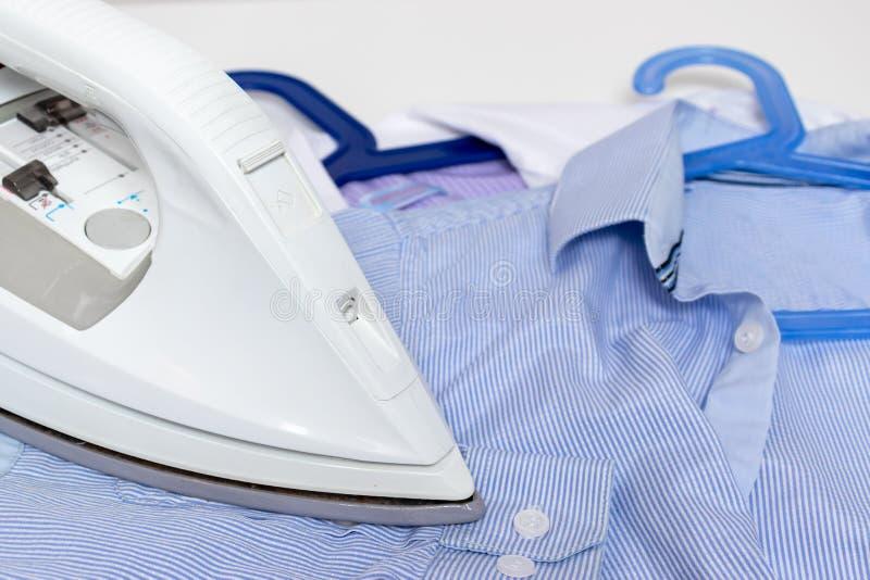 Fim elétrico moderno branco do ferro acima e camisas azuis na tabela - passar, lavanderia e conceito dos trabalhos domésticos imagem de stock