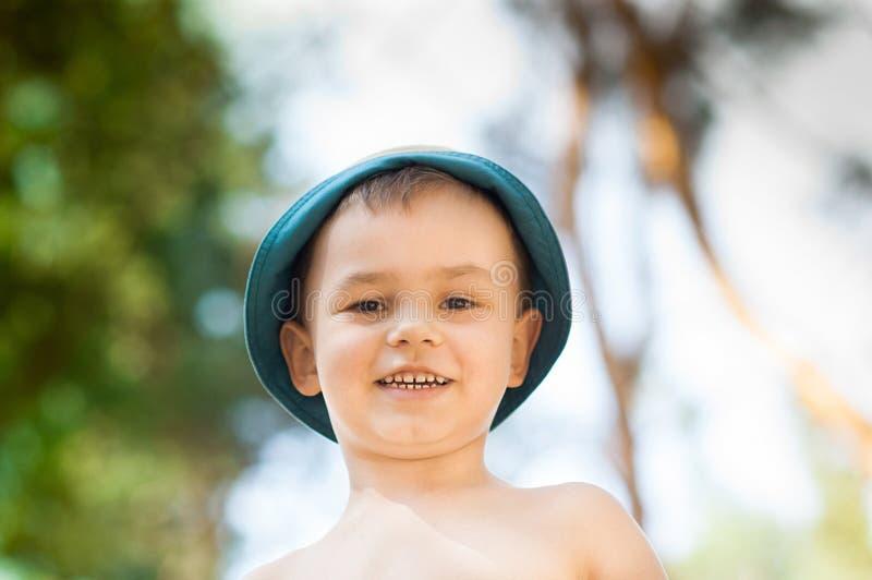 Fim exterior acima do retrato do rapaz pequeno em um chapéu Fundo, uma pessoa, criança, 4-5 anos velha, smilling feliz fotos de stock