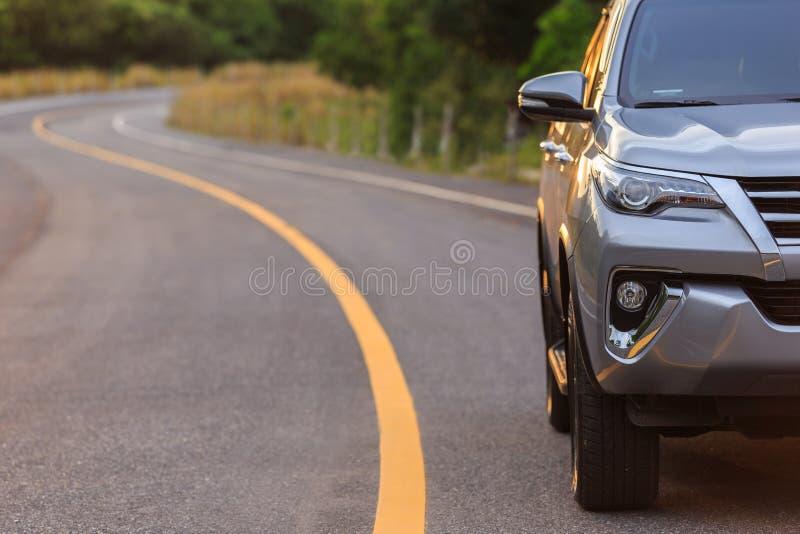 Fim honesto do estacionamento de prata novo do carro de SUV na estrada asfaltada imagem de stock