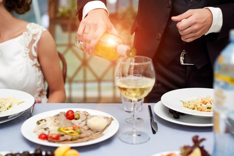 Fim horizontal acima do homem caucasiano no terno preto e na camisa branca que derramam o vinho cor-de-rosa em um vidro alto de u imagens de stock