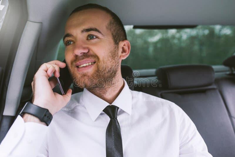 Fim horizontal acima do retrato de um homem de negócios de sorriso caucasiano considerável que chama o telefone esperto e que sen foto de stock