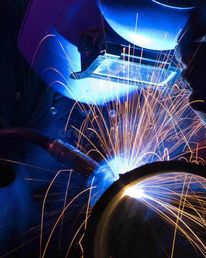 Fim iluminado azul do soldador do MIG fotos de stock