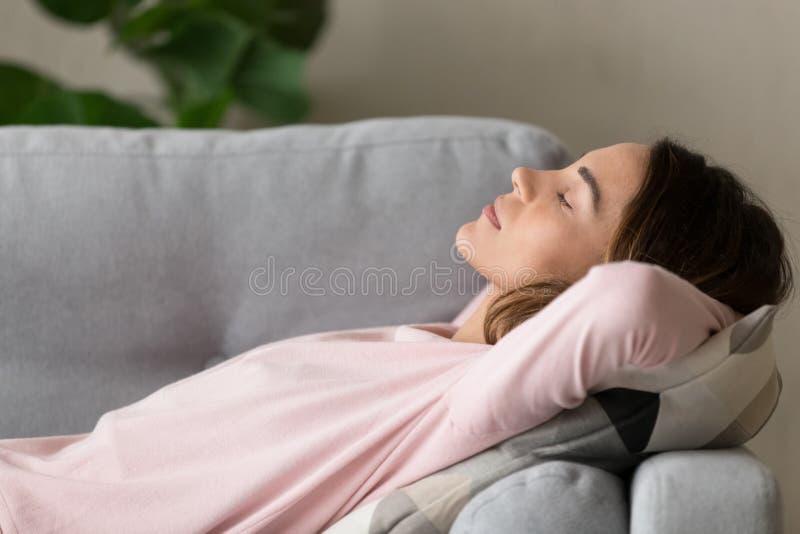 Fim lateral acima da mulher da vista que tem a sesta do dia no sofá fotos de stock royalty free