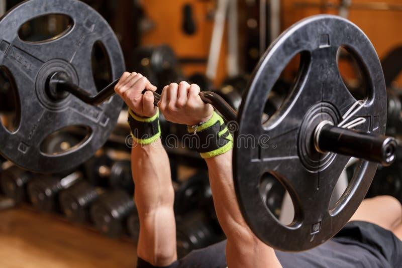Fim muscular novo considerável do homem acima, fazendo o exercício francês da imprensa do banco com o barbell no gym imagens de stock