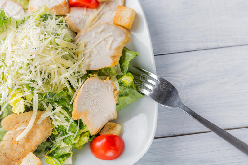 Fim orgânico verde saudável da salada de caesar acima na placa e na forquilha brancas fotografia de stock