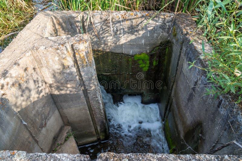 Fim permeável do eixo da água concreta acima, a água suja de uma lagoa pequena que flui para fora a uma angra pequena fotos de stock