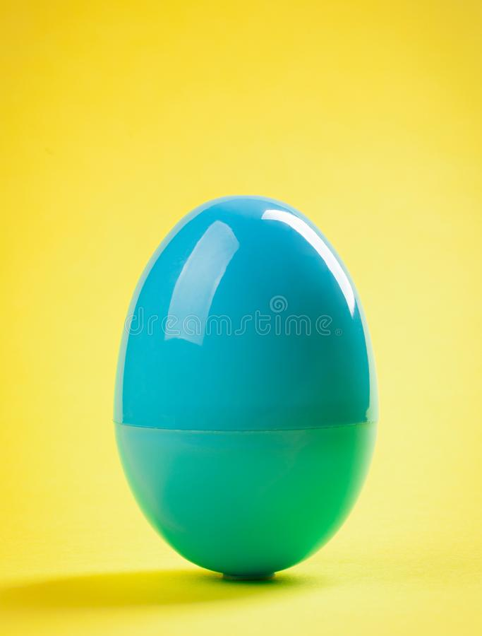 Fim plástico azul do ovo acima no fundo amarelo imagem de stock royalty free