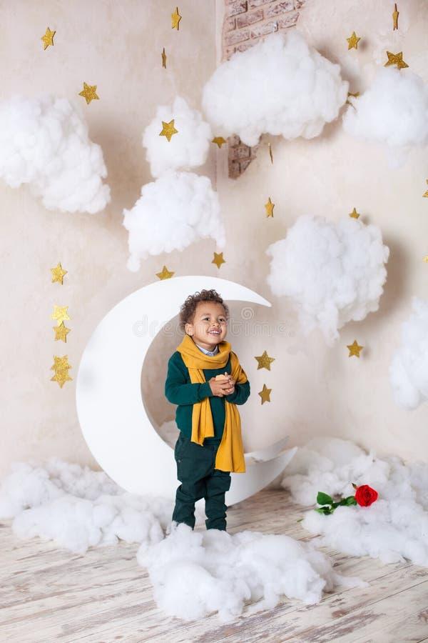 Fim preto do menino acima do retrato Retrato de um menino de sorriso alegre em um lenço amarelo Inf?ncia Pouco menino preto com u fotografia de stock