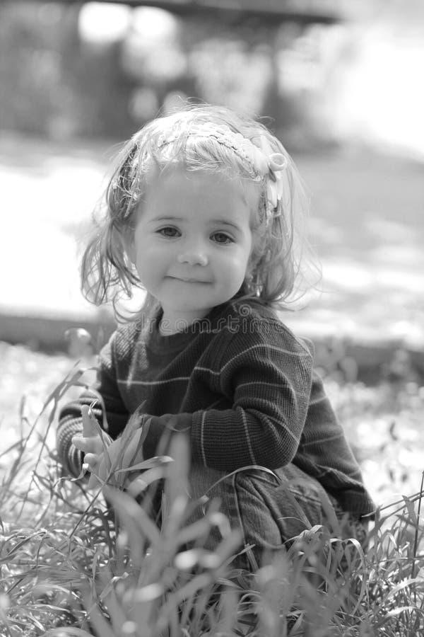 Fim preto e branco acima da menina pequena extremamente bonito do bebê de um ano que senta-se na grama imagens de stock royalty free