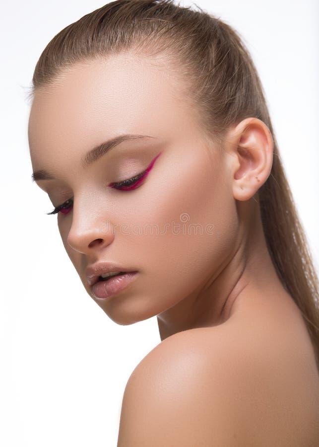 Fim roxo ou magenta do encanto da seta da composição com os pregos vermelhos da forma na cara Mulher com pele perfeita Tiro macro fotografia de stock