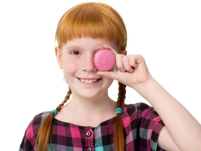 Fim ruivo pequeno da menina um bolo do olho foto de stock