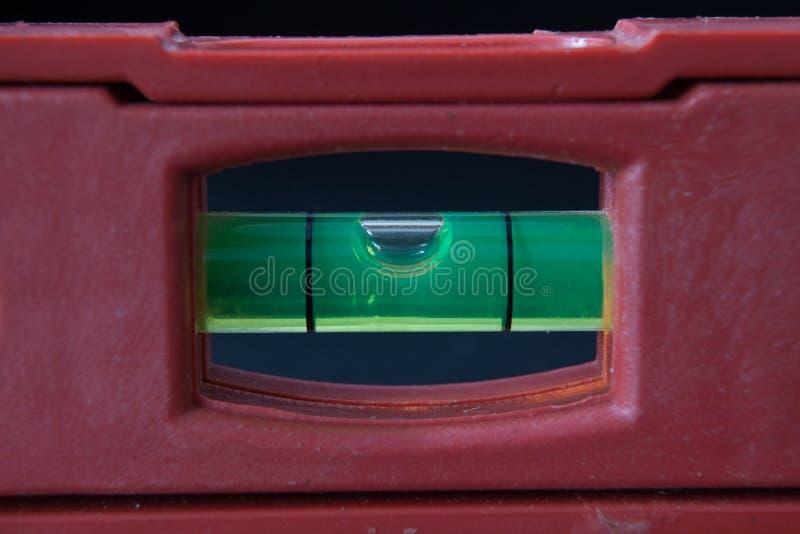 fim vermelho da régua do equilíbrio do nível da construção acima no fundo preto fotografia de stock royalty free