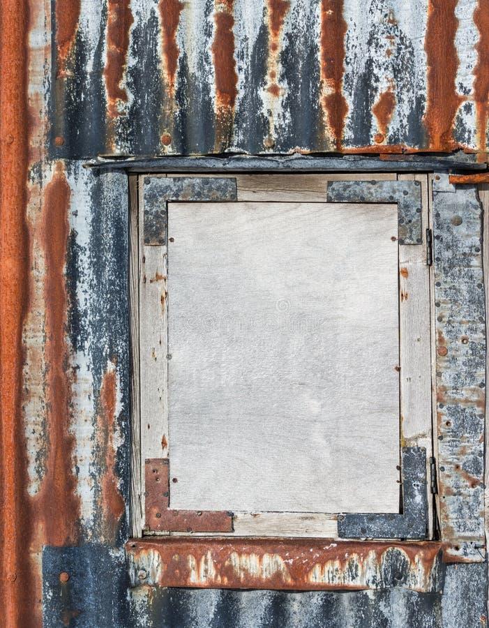 Fin abstraite de l'entourage rouillé de fer ondulé embarqué vers le haut de la fenêtre images libres de droits