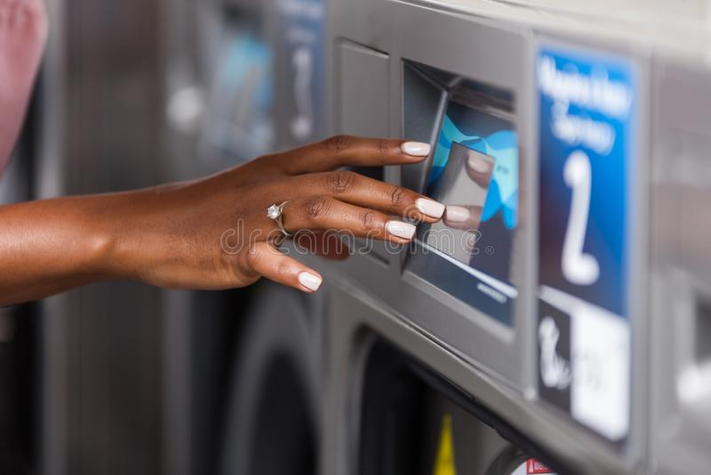 Fin américaine de main de femme de jeune africain noir utilisant une machine à laver dans une blanchisserie photographie stock libre de droits