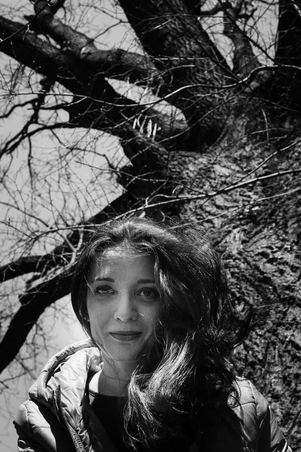 Fin blanche et noire vers le haut de portrait d'outdoos de jeune fille smilling dans la veste se reposant près du grand vieil arb images libres de droits