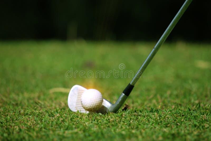 Fin brouill?e de club de golf et de boule de golf dans le domaine d'herbe avec le coucher du soleil photos stock