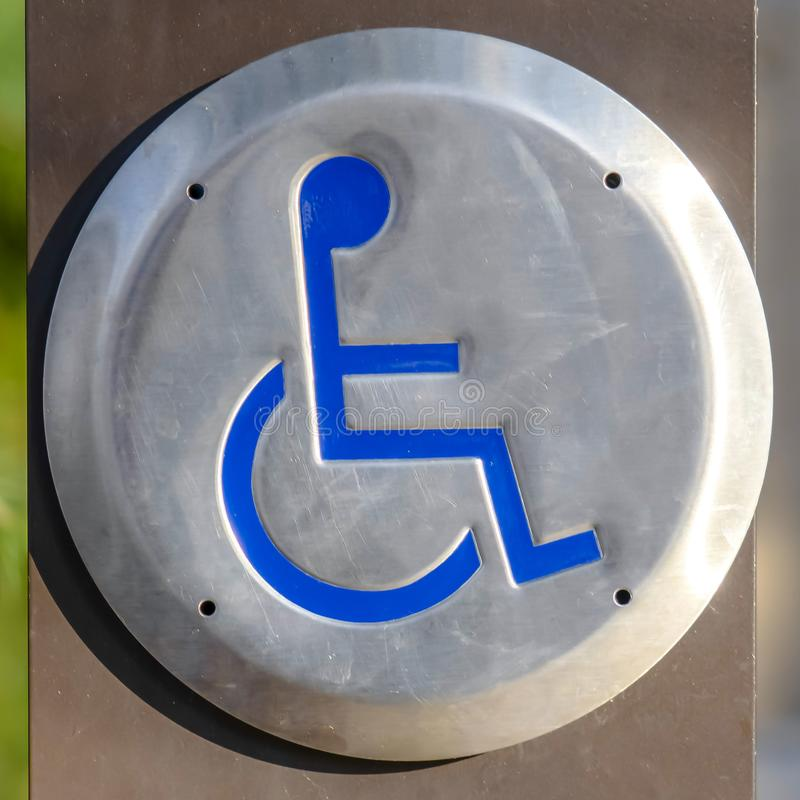 Fin carrée d'un signe handicapé gravé sur un métal circulaire vu un jour ensoleillé photographie stock libre de droits