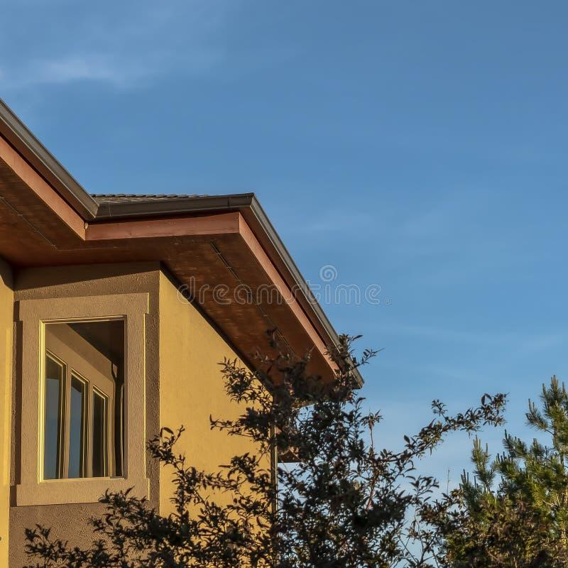 Fin carrée de cadre d'un extérieur supérieur à la maison d'étage avec les arbres et le ciel bleu un jour ensoleillé images libres de droits