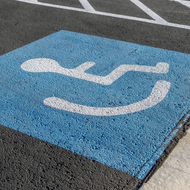 Fin carrée de cadre d'une personne sur une icône de fauteuil roulant peinte sur le trottoir noir images stock