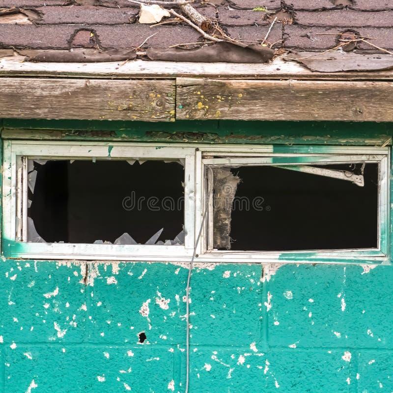 Fin carrée de cadre de la petite fenêtre avec le verre cassé d'un vieux et superficiel par les agents hangar photos stock