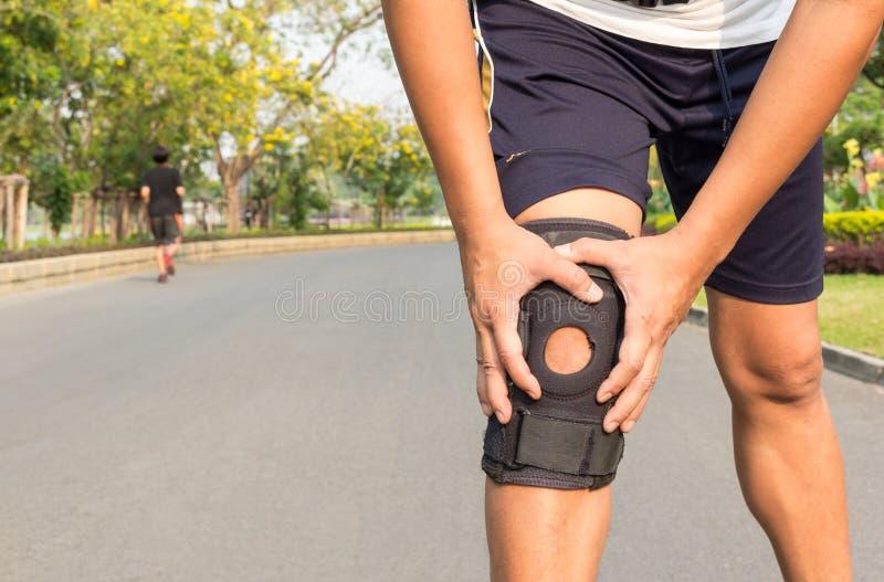 Fin d'accolade de soutien de genou sur la jambe au parc public image stock