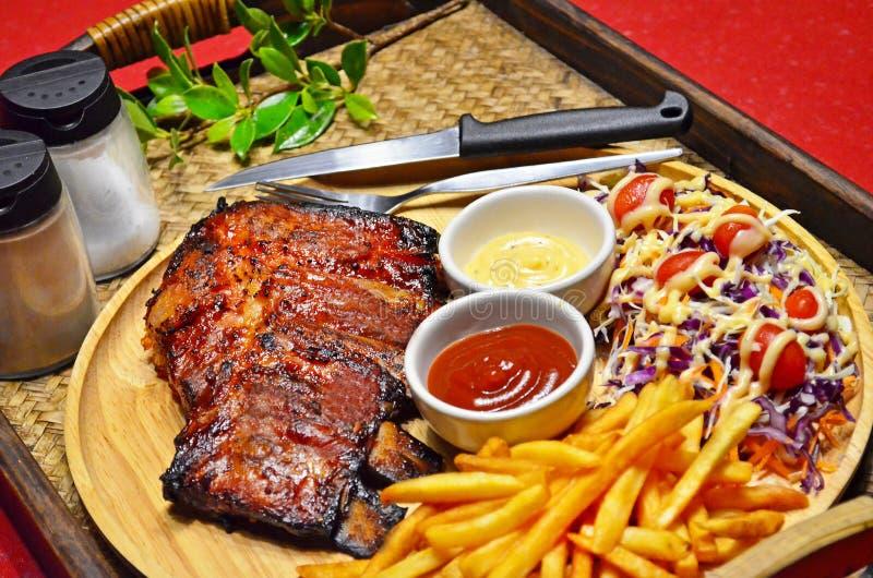 Fin d'ensemble de bifteck grillé par NERVURES de BBQ avec le français frit et la salade sur Tray Background en bambou photographie stock libre de droits